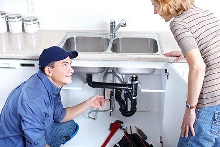 plombier qui répare une fuite d'eau sous évier