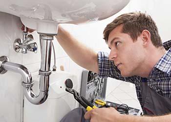 plombier qui répare le siphon d'un évier