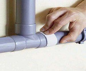 Plombier qui procède au colmatage d'un tuyau d'un robinet