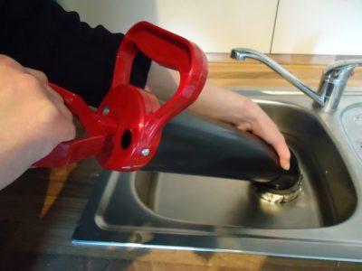 Plombier débouche un évier cuisine avec une pompe à vide