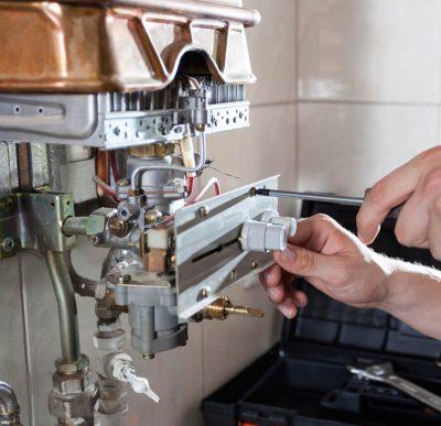 chauffagiste qui répare un boiler