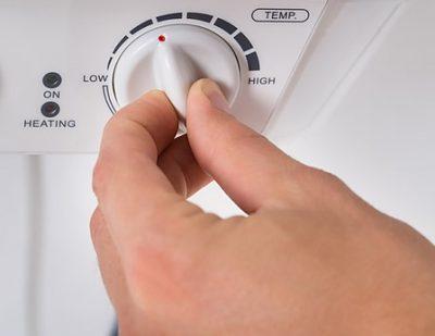Chauffagiste régle le thermostat de la chaudière