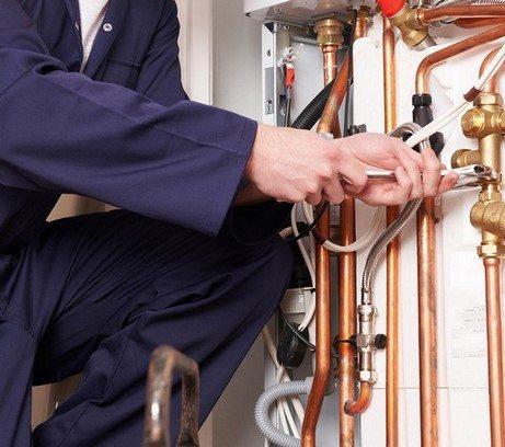 Chauffagiste assure le raccordement des tuyaux de la chaudière