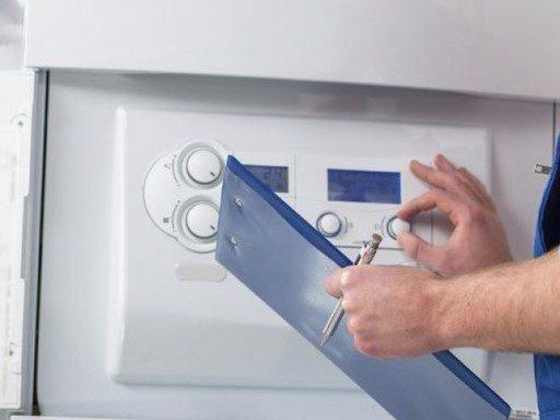 Le chauffagiste règle le thermostat de la chaudière