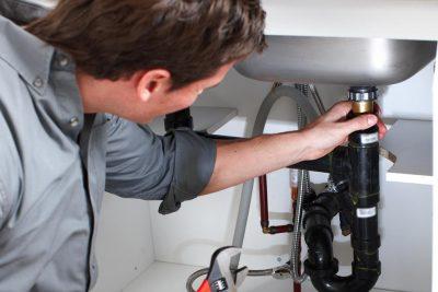 Plombier assure les raccordements tuyaux d'un évier cuisine