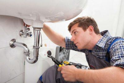 Plombier fixe les tuyauterie du lavabo