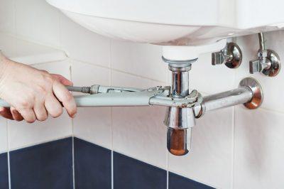 Plombier fixe la tuyauterie du lavabo