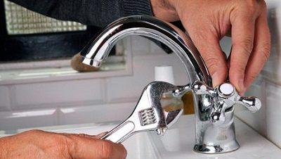 Plombier qui répare une fuite robinet