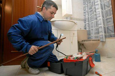 plombier qui répare la tuyauterie