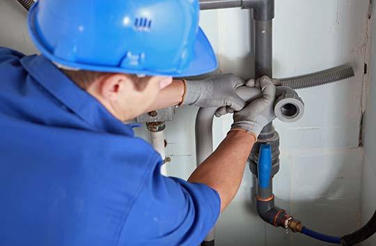 plombier qui répare tuyaux