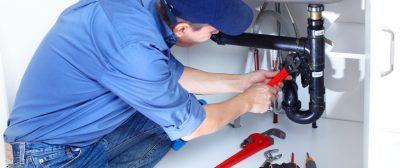 Plombier qui répare une fuite au niveau de la tuyauterie douche