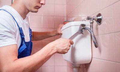 Plombier qui répare une fuite wc