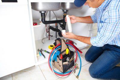 plombier qui remplace une tuyauterie