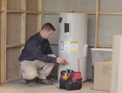 technicien chauffagiste qui répare un chauffe-eau