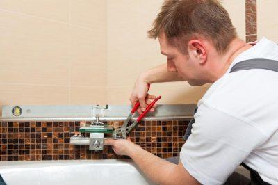 plombier qui répare la robinetterie de la baignoire